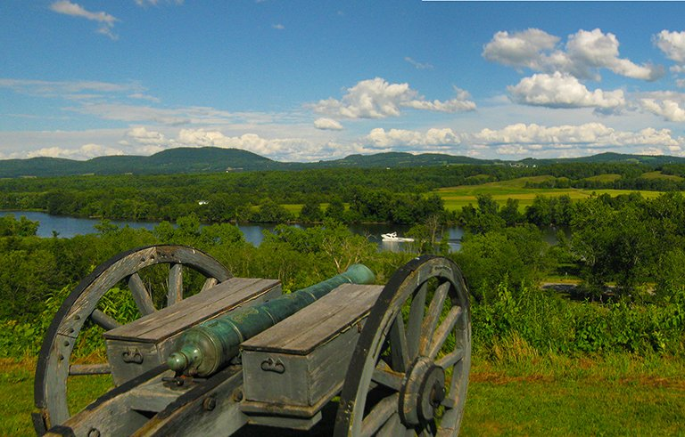 A cannon on a dark wooden carriage on a ridge top overlooks a river, with green hills and fields, and blue sky, in the background.