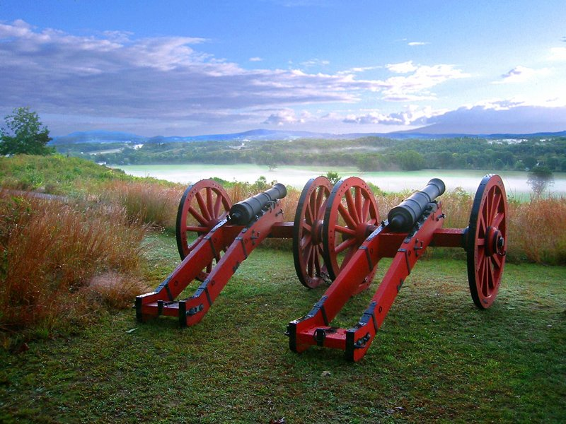 Two cannons on red carriages sit on a grassy ridge top overlooking a foggy valley below, with hills and clouds in the distance.