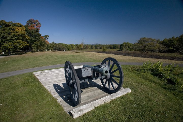 A small cannon on a gray carriage sits on a wooden platform in a green field, with early autumn trees and a clear blue sky in the background.