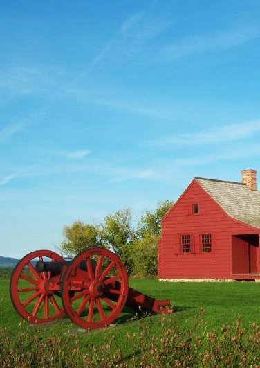Neilson House: a small red historic house on the right and a cannon on the left, both on a small grassy ridge top.