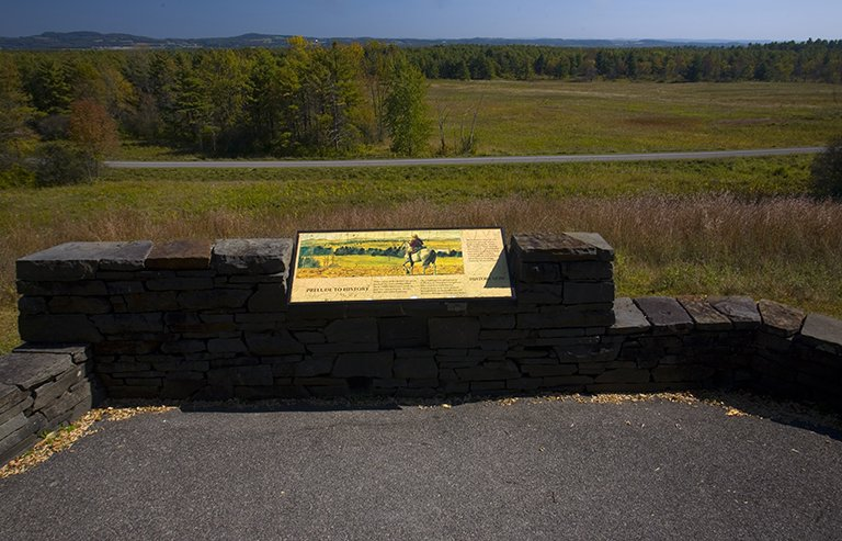 A paved walkway platform with a stone wall and informational sign, overlooking fields, woods, and a small paved road.