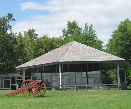 A side view of a building with glass window sides, a cannon in the foreground, and a grassy lawn. Trees and a partly cloudy sky in the background.