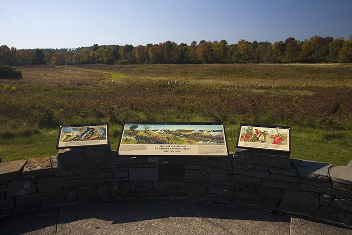 A low stone wall with three informational signs, overlooking a large grassy field and a tree line in the background.