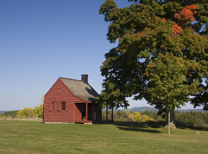 A small red historic house, slightly in the shade of a large maple tree, on a grassy lawn. Clear blue skies and a low mountain ridge are in the background.